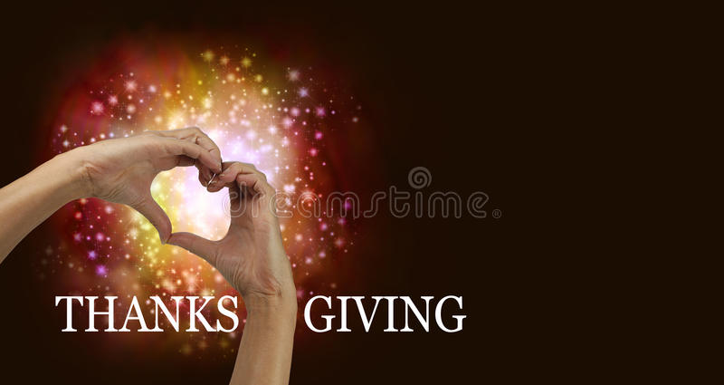 Thanksgiving Heart Hands. Pair of female hands making a heart shape with red orange colored sparkles behind, on a dark background with copy space and the word '
