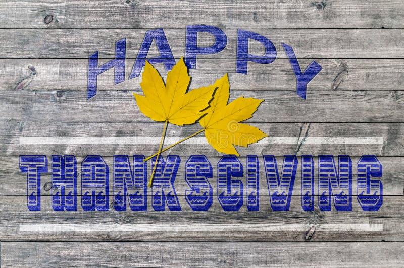 Thanksgiving heureux bleu sur le fond en bois avec deux feuilles jaunes photographie stock
