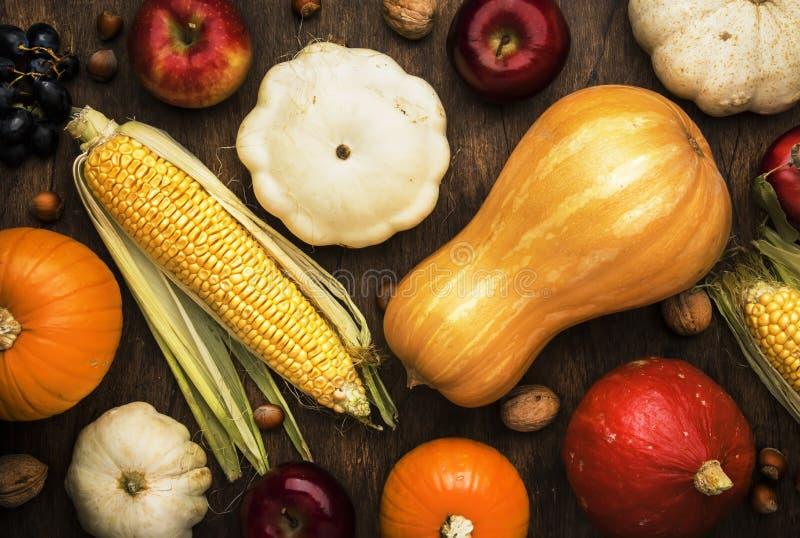 Thanksgiving-Hintergrund, Konzept der Herbsternte Rustikaler Tisch mit Äpfeln, Kürbissen, Nüssen, Trauben und Mais auf dunklem Ti lizenzfreie stockfotografie