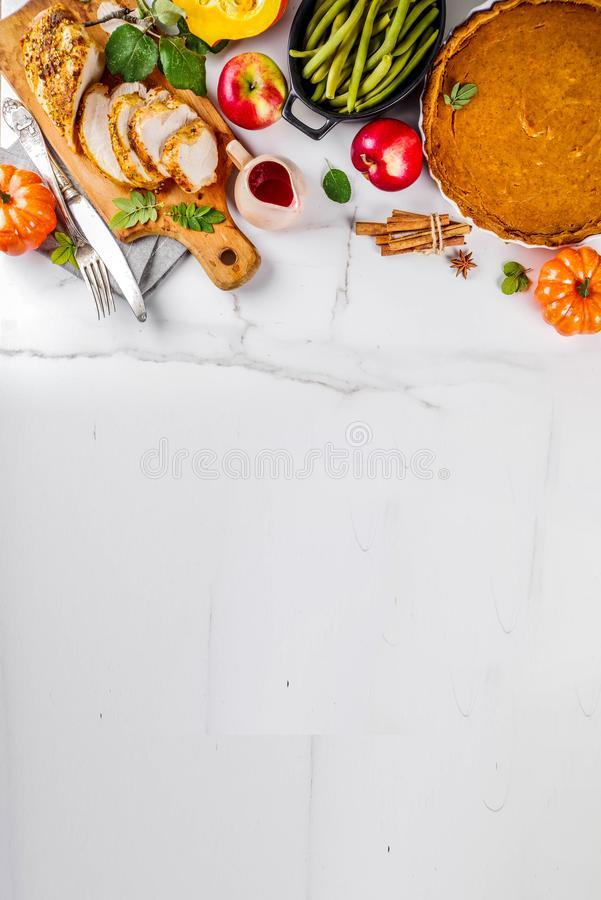 Thanksgiving holiday food. Thanksgiving holiday table with traditional festive food - turkey, pumpkin pie, pumpkins, green beans, cranberry sauce, corn, autumn royalty free stock image