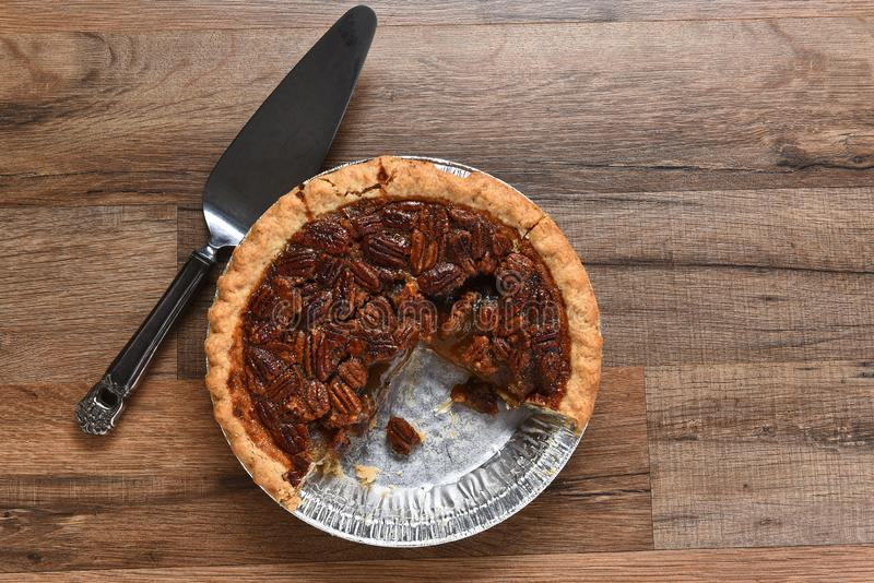 A Thanksgiving holiday pecan pie in tin with piece missing stock images
