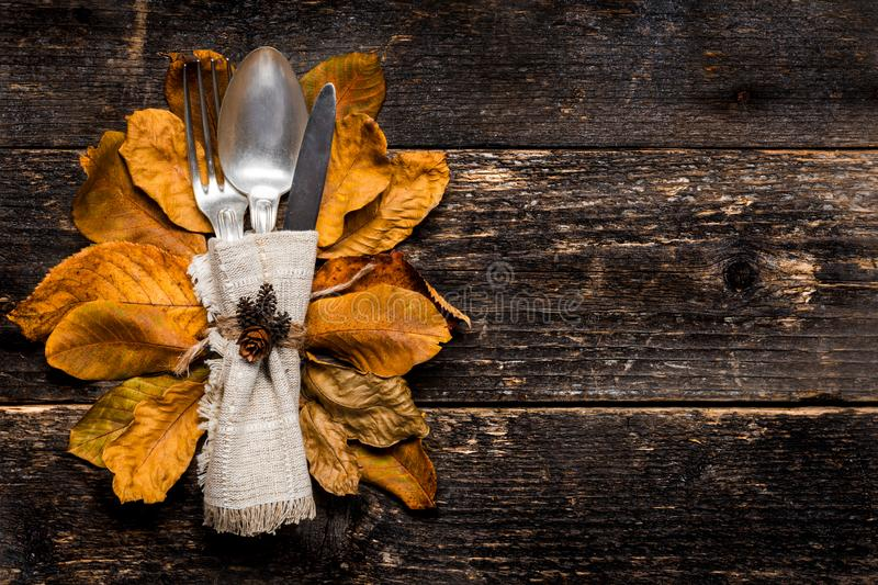 Thanksgiving Meal Setting. Seasonal table setting. Thanksgiving autumn place setting with cutlery and colorful fall fall leaves. stock photos