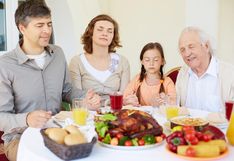 Thanksgiving pray. Portrait of family of four praying at festive table on Thanksgiving day stock image