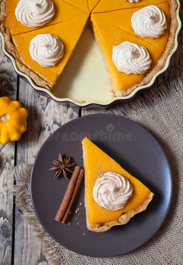 Thanksgiving pumpkin halloween pie with whipped cream and cinnamon on rustic background, top view stock image