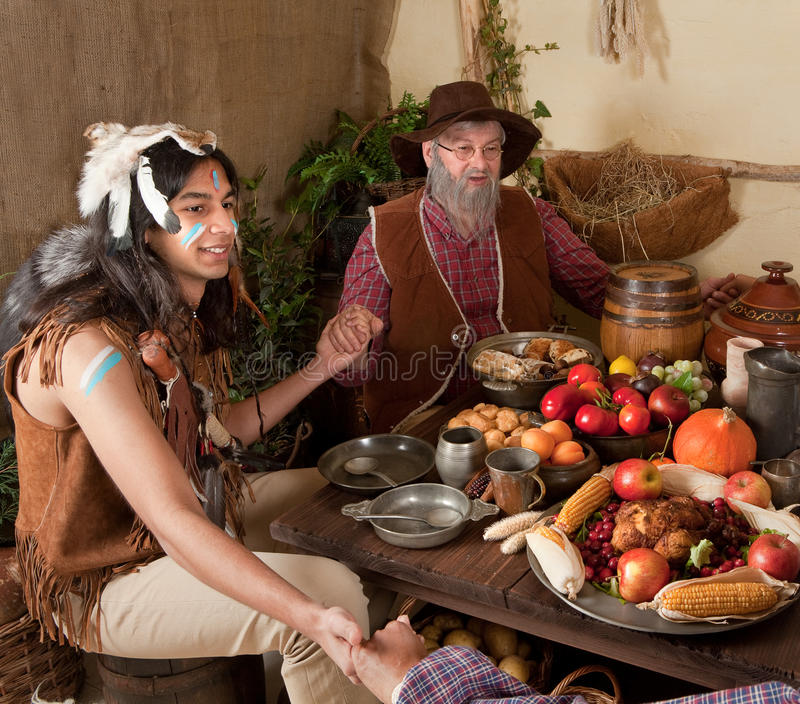 Thanksgiving reenactment. Reenactment scene of the first Thanksgiving Dinner in Plymouth in 1621 with a Pilgrim family and a Wampanoag Indian royalty free stock image