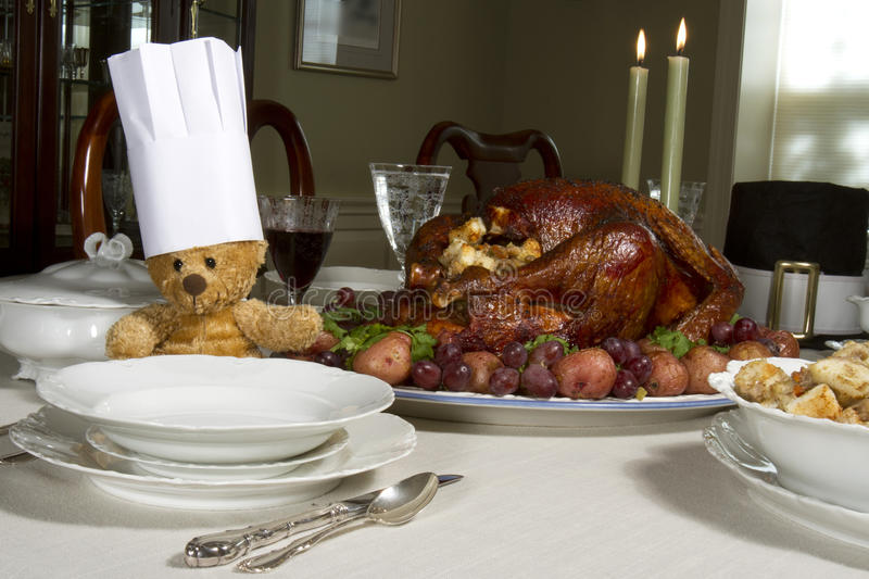 Thanksgiving Table with Chef Bear. Table laden with Thanksgiving feast with a teddy bear wearing a chef's hat stock photography