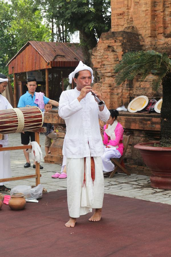 Thap Ba Ponagar, Nha Trang, Viet Nam - May 22,2018: The man in white long dress is playing the Champa bugle of Champa people at Th. This is a traditional bugle royalty free stock images