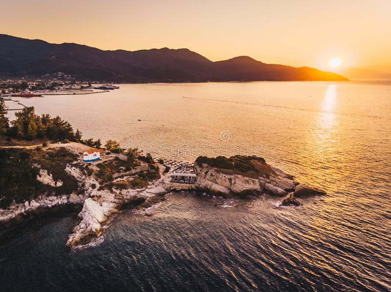Thasos Beach Karnagio at sunset and Limenas town visible to the left. Thasos or Thassos Island is a summer destination island in the Aegean Sea popular for stock photos