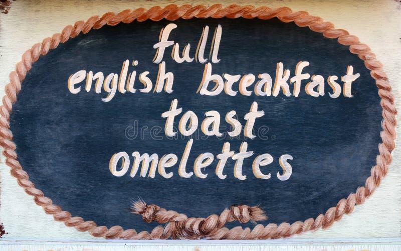 THASSOS, GRECIA 13 de septiembre de 2015: Una muestra de madera fuera de un restaurante, desayuno inglés lleno, tostada, tortilla imagenes de archivo