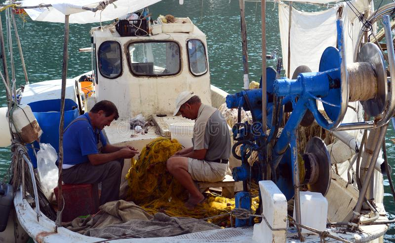 Fishermen collect the fish in nets after fishing in his boat stock images
