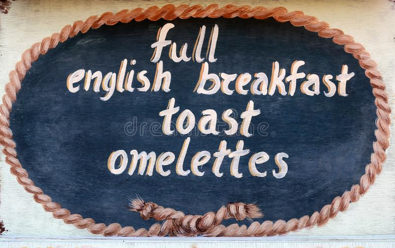 THASSOS, GREECE- September 13, 2015: A wooden sign outside a restaurant, full english breakfast, toast, omelettes stock images