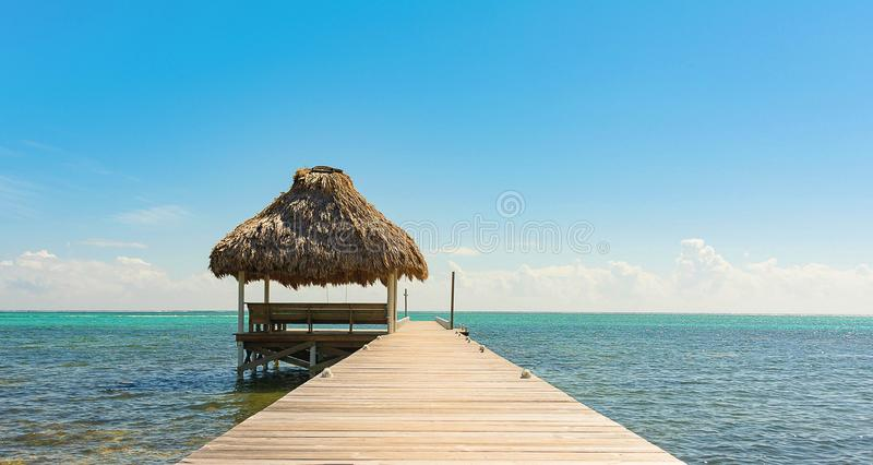 Pier with Thatch Cabana. Thatch Cabana at the end of the wooden pier in the Caribbean. Turquoise water on the horizon stock photos