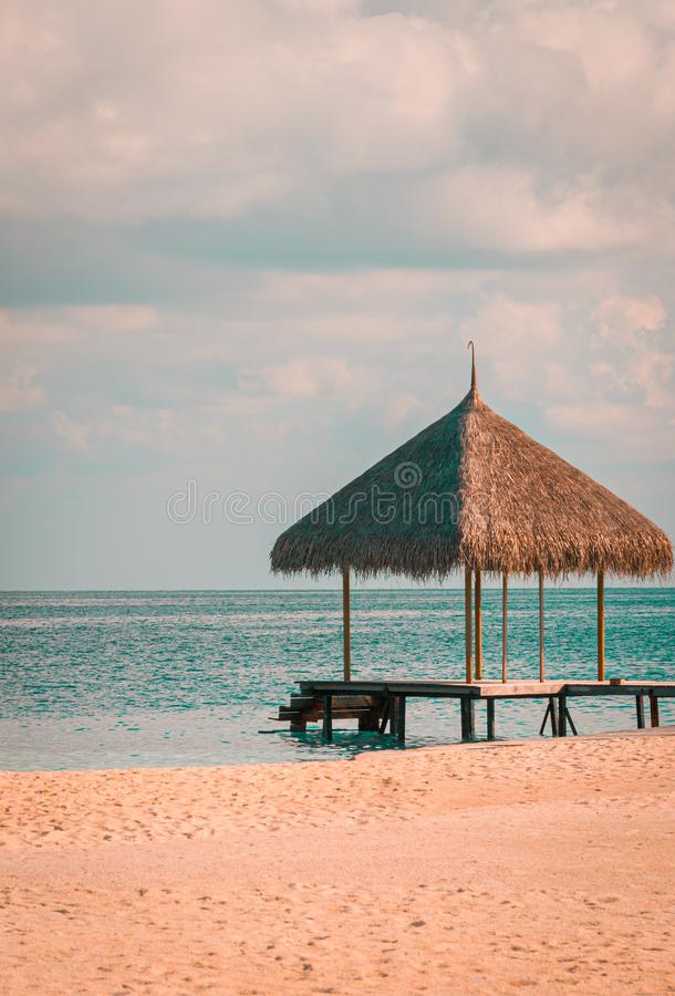 Thatch Cabana at the end of the wooden pier in the THe Maldives. Torquoise water on the horizon. Thatch Cabana at the end of the wooden pier in the MAldives royalty free stock photos