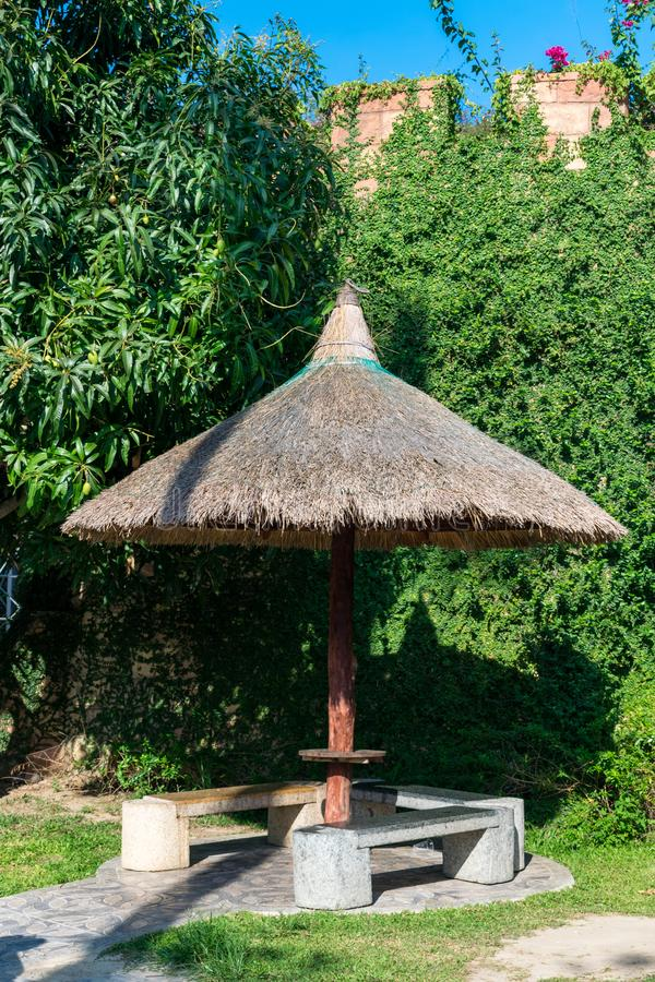 Thatch canopy with stone benches the background of an overgrown wall royalty free stock image