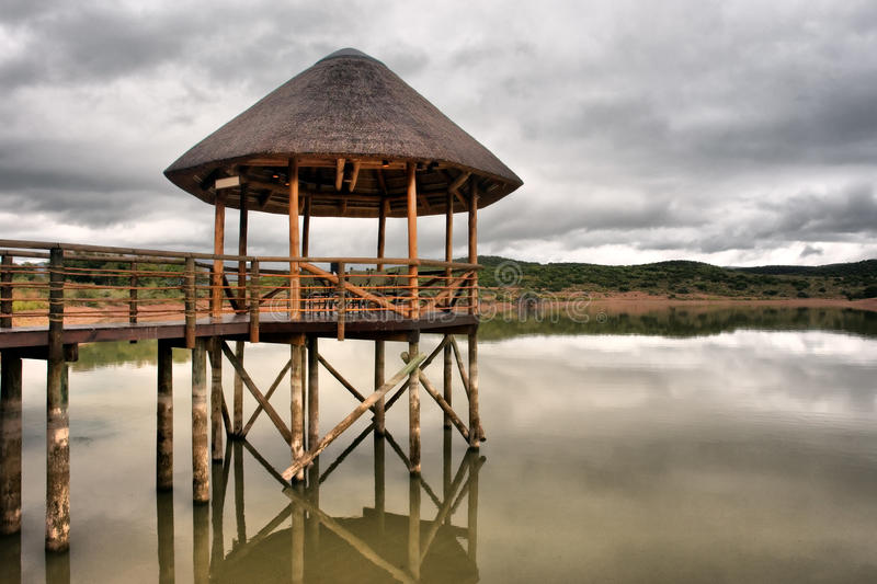 Thatch pavilion on lake in Karoo. Shot in a game lodge near Oudtshoorn, Western Cape, South Africa royalty free stock image