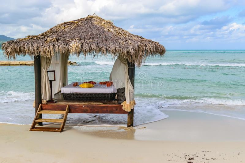 Thatch roof hut massage bed on tropical island white sand beach. Luxury vacation resort spa pampering royalty free stock photography