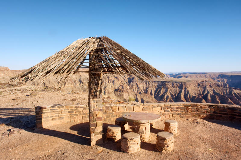 Thatch-roofed umbrella against canyon. Shot in Fish River Canyon National Park, Namibia stock image