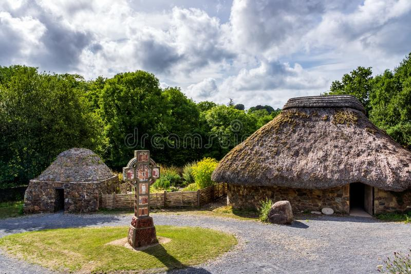 Thatch and stone cottage with Celtic cross in centre, concept of early age human settlement. Ancient thatch and stone cottage with Celtic cross in centre stock images