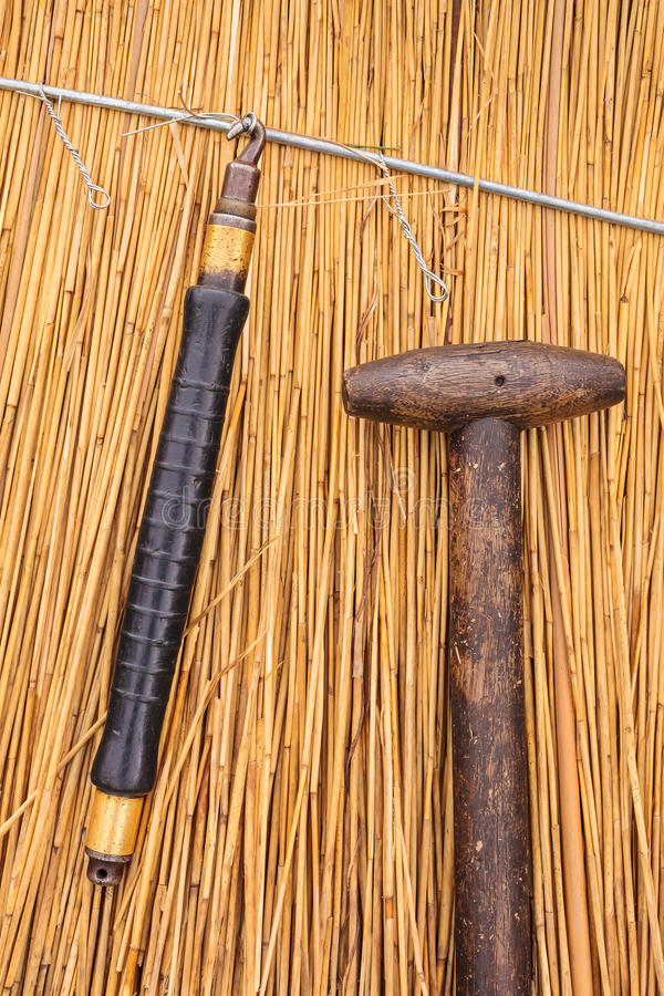 Thatch tools in front of a newly thatched roof. Traditional thatch tools in front of a newly thatched roof royalty free stock images