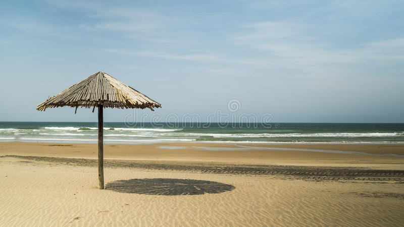 Thatch umbrella on the beach. The beautiful beach of Durban, South Africa, with a thatch umbrella casting shade, with the blue sea in the background royalty free stock photos