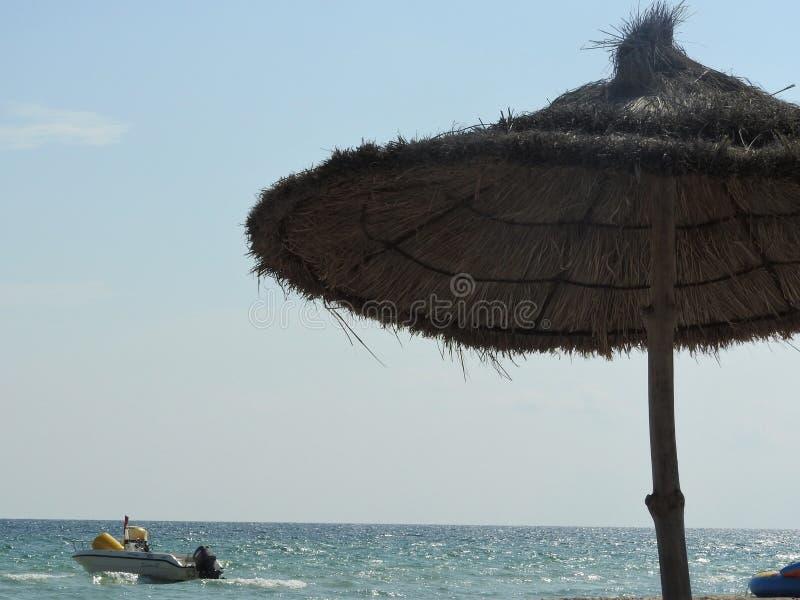 Thatched beach umbrellas on the beach Tunisia Djerba.  stock photography