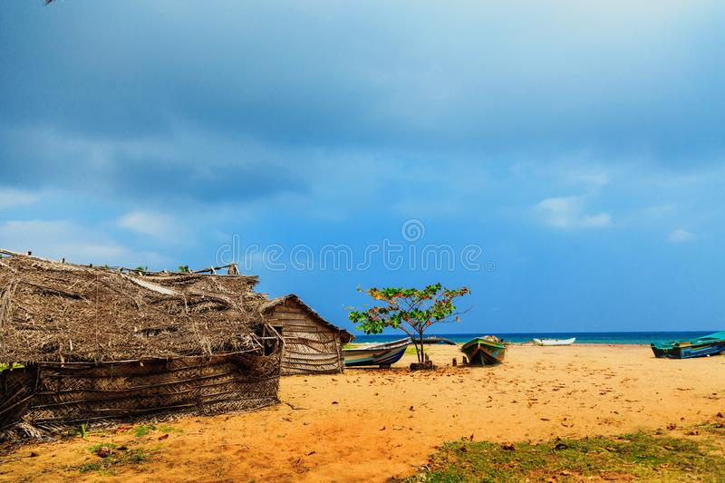 Thatched coconut leaf house or fishing hut and boats on tropical beach royalty free stock image
