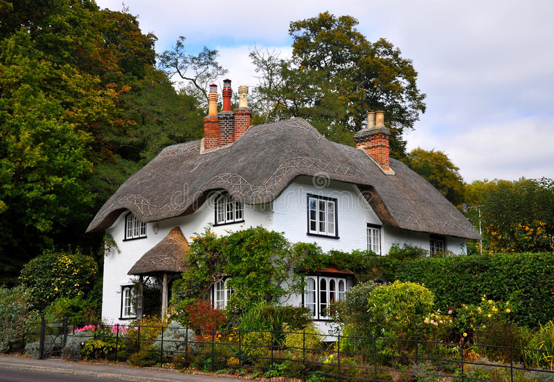Thatched Cottage. Old english thatched cottage with pretty garden and large trees behind stock image
