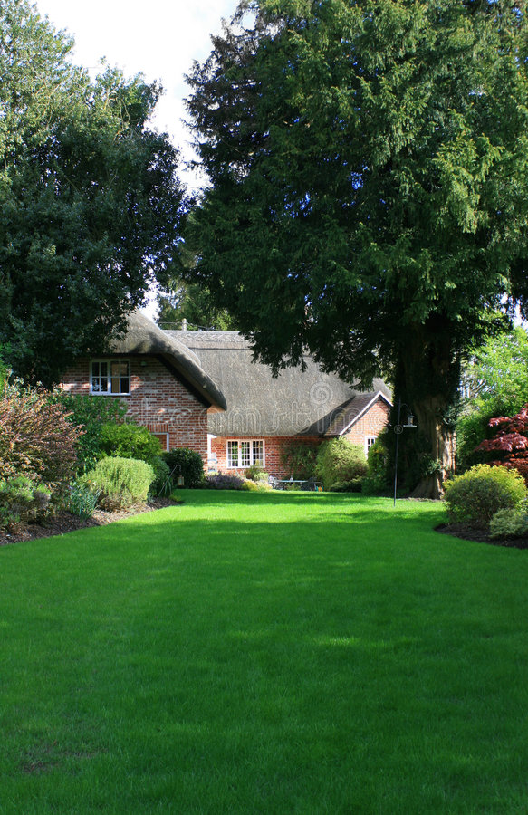 Thatched cottage garden stock image