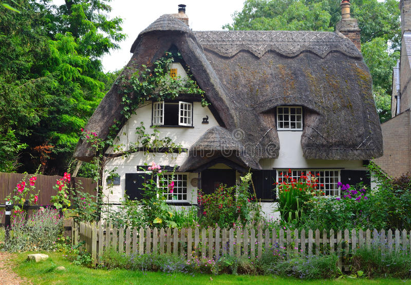 Thatched cottage with white walls and colourful garden. Houghton, Cambridgeshire, England - July 20, 2016: Thatched cottage with white walls and colourful royalty free stock photos