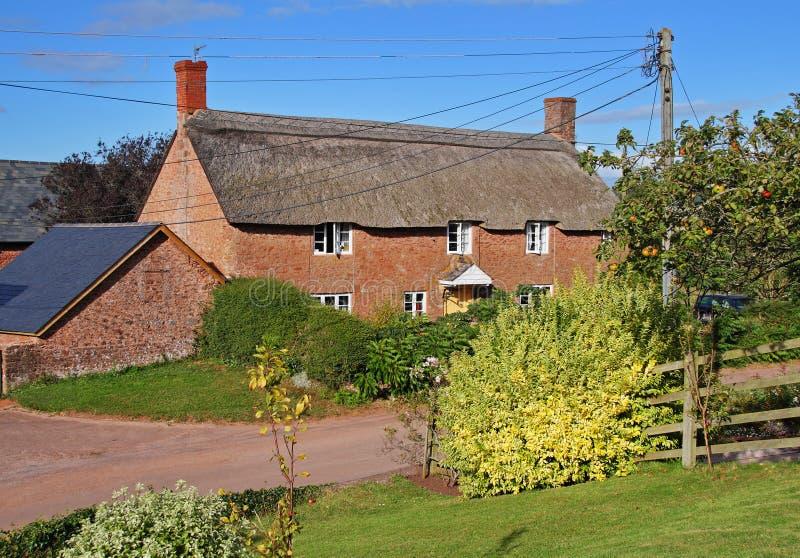 Thatched Dorf-Häuschen nahe bei einem landwirtschaftlichen Weg lizenzfreies stockfoto