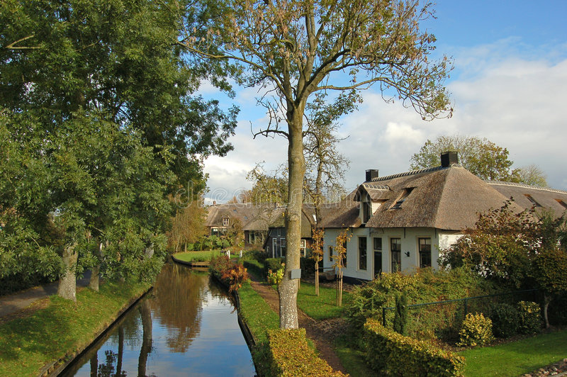 Thatched house on waterside royalty free stock image