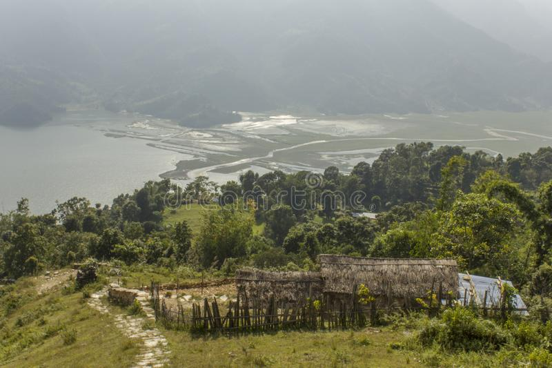Thatched hut on the green hillside against the backdrop of a misty mountain valley with a lake and a river. A thatched hut on the green hillside against the royalty free stock photography