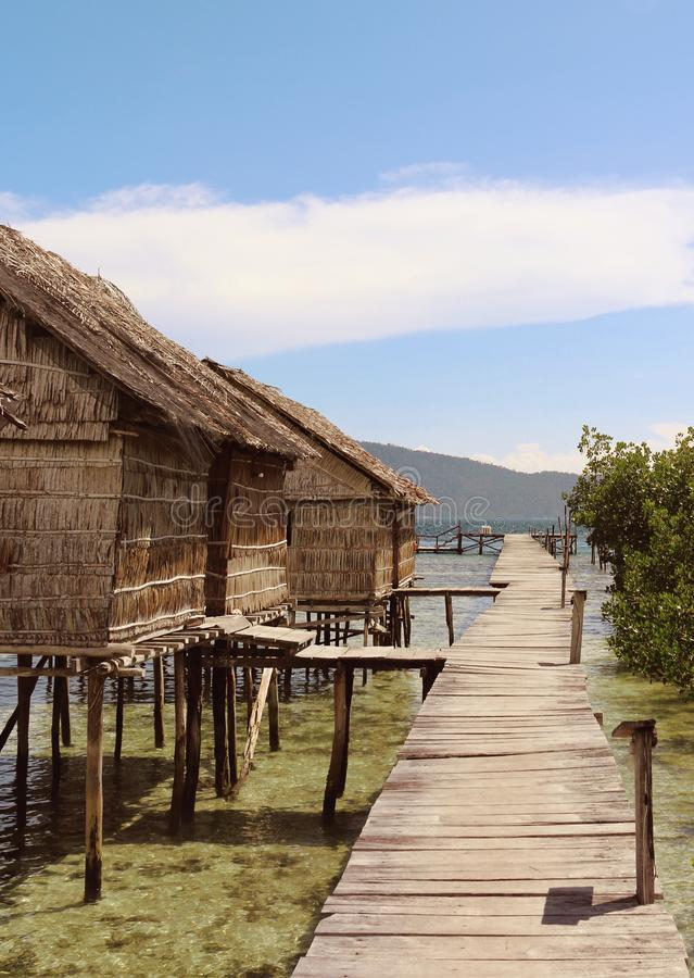 Thatched Hut on a Pier in Gam Islands, Raja Ampat. Huts with thatched roof and walls on the pier of Gam Islands in Raja Ampat, West Papua above the calm tropical stock image