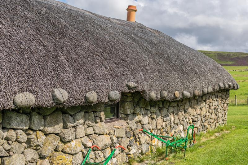 A thatched long house with chimney and traditional farm machinery royalty free stock image