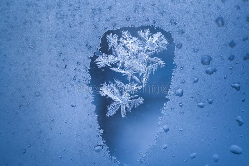 Thawed spot on frozen winter window with frosty pattern inside it. Thawed spot on frozen winter window with frosty pattern like snowflake inside it royalty free stock photo