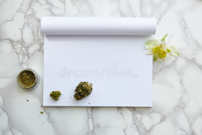 THC/CBD Cannabis Flower and Joint on Drawing Notepad. THC and CBD Cannabis Flower and Joint on Drawing Notepad on marble table. Blank space for text stock photos