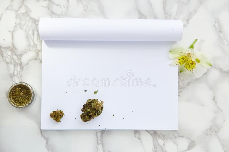 THC/CBD Cannabis Flower and Joint on Drawing Notepad. THC and CBD Cannabis Flower and Joint on Drawing Notepad on marble table. Blank space for text stock images