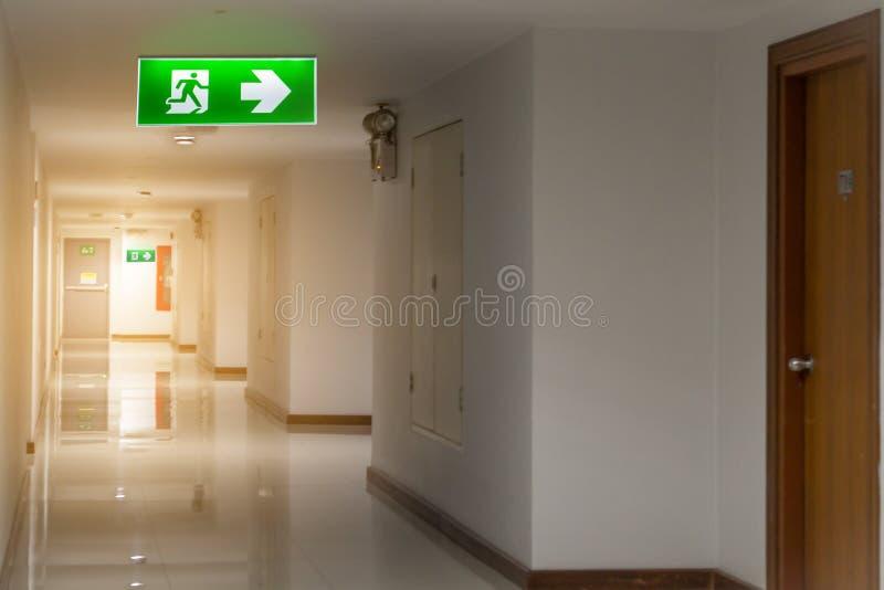 The绿色紧急出口标志在显示方式的旅馆里逃脱 图库摄影