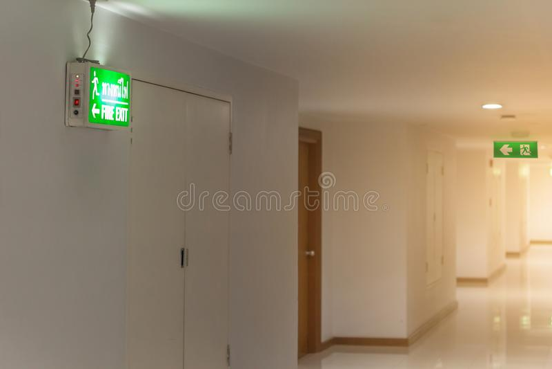 The绿色紧急出口标志在显示方式的旅馆里逃脱 库存照片