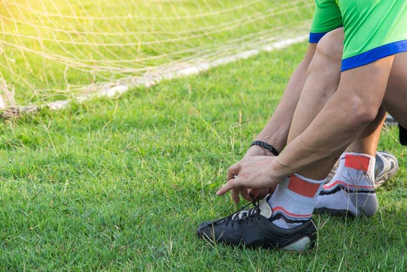 The†‹atlety Młody azjatykci mężczyzna wiąże futbol buty obok pola, męskiego futbolu gotowego dla sztuki na polu, wellness i spo zdjęcia royalty free