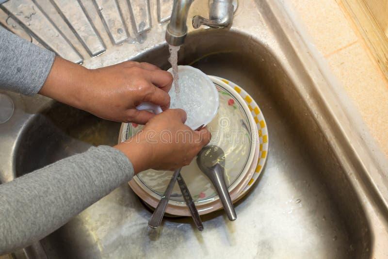 TheHand het schoonmaken van wijfje of huisvrouwen de schotels van de vrouwenwas met een gele spons in keuken daalt stock afbeeldingen