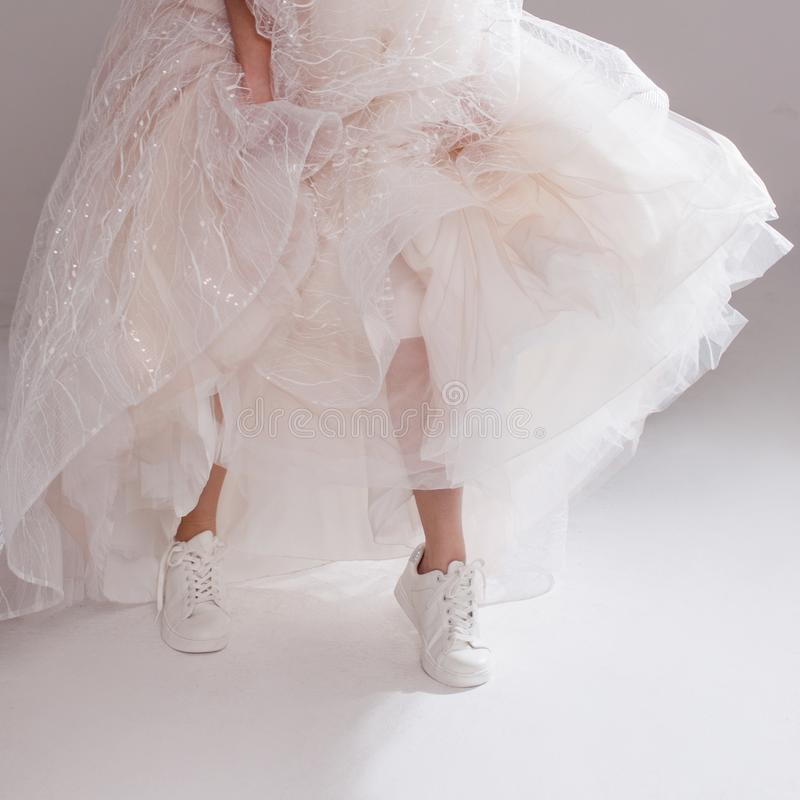 Free The Girl In Magnificent Wedding Dress And White Sneakers, Legs Close-up. Runaway Bride Stock Photos - 117564943
