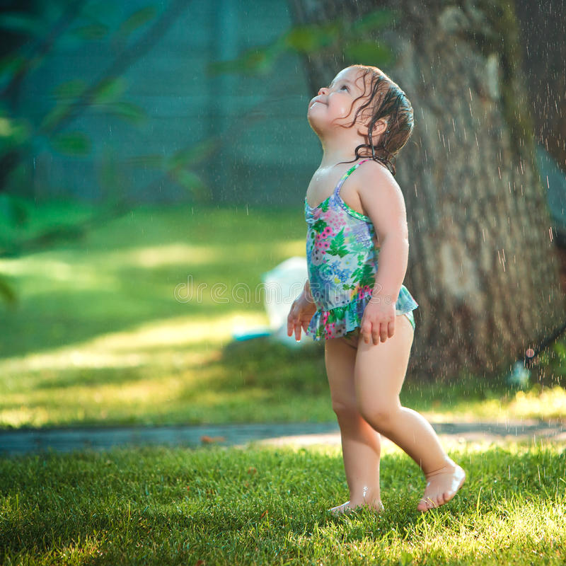 Free The Little Baby Girl Playing With Garden Sprinkler. Royalty Free Stock Image - 74812856