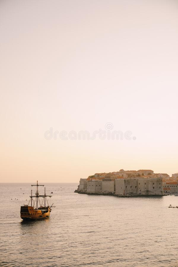 Free The Old City Of Dubrovnik Against The Sunset Sky. The Wooden Sailing Ship Galleon Approaches The Main Pier Of Dubrovnik. Stock Photography - 184002282