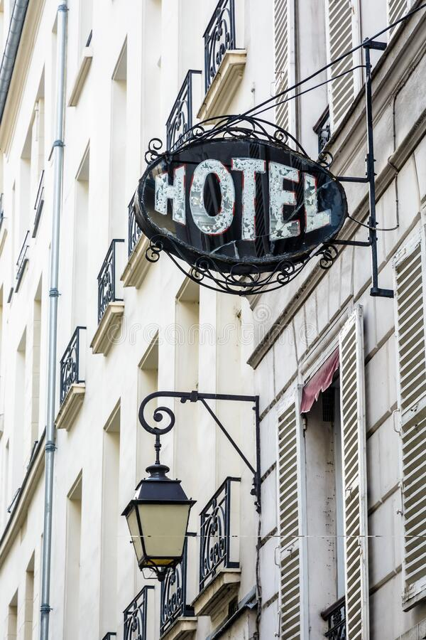 Free The Worn Period Sign Of An Hotel And A Vintage Street Light Fixed To An Old Building In Paris Stock Photos - 181791533