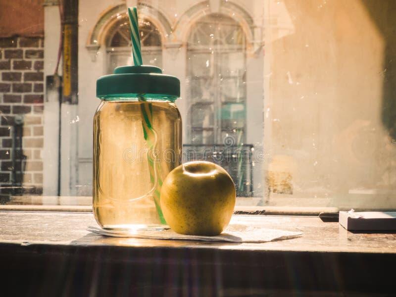 Thea van de glaskruik chamomille met appel op de houten ochtend van de lijst zonnige dag royalty-vrije stock foto