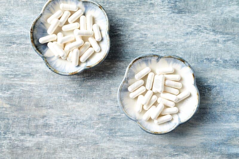Theanine kapslar Dietary supplement lantligt tr? f?r bakgrund arkivfoto