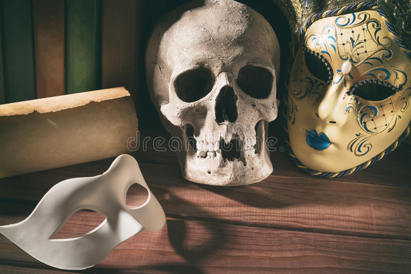 Theater and drama concept. Human skull, venetian masks with old scroll and books on wooden table royalty free stock image