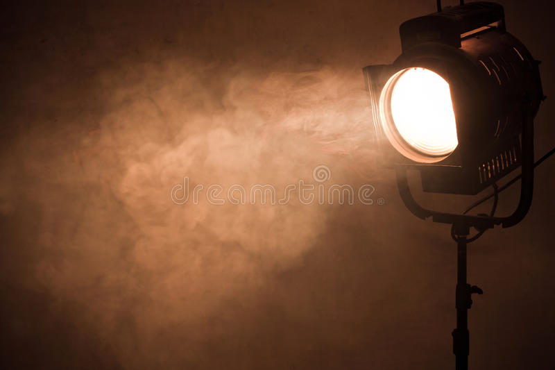 Theater spot light with smoke against grunge wall. Theater spot light with smoke against wall stock photo