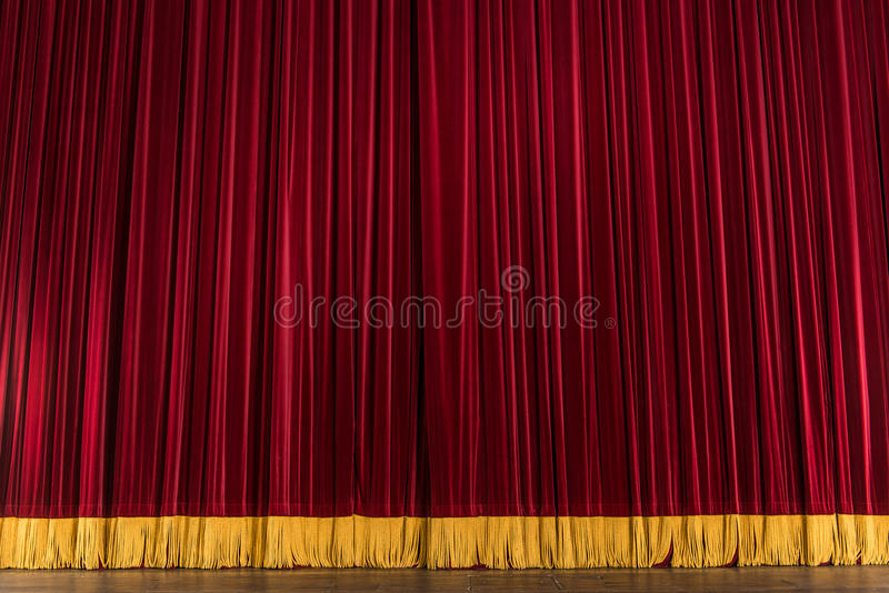 Theater stage curtain. Red theater stage curtain with golden bottom trim royalty free stock photography